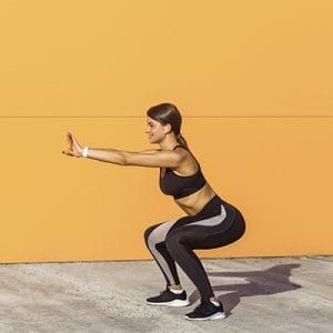 wall sit — woman doing a wall sit against an orange wall