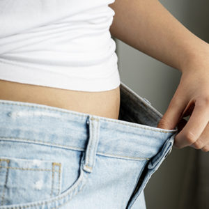 A women wearing a with top pulling her jeans away from her waste to show she's lost a lot of weight thanks to these weight loss tips