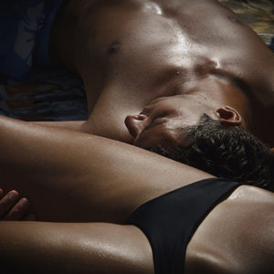 Dark-lit image of a woman and man cuddling in their underwear