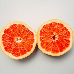 A grapefruit cut in half to represent breasts and nipples that are itchy