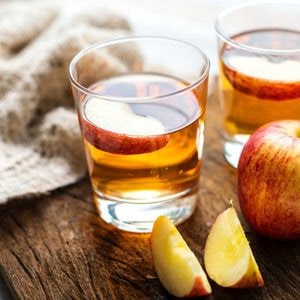 apple cider vinegar in two glasses sitting next to a sliced red apple on top of a wooden cutting board