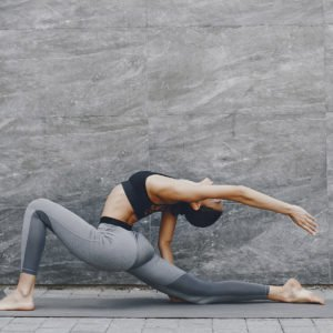 a woman wearing grey against a grey background doing yoga poses to aid her digestion