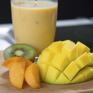 A mango protein smoothie on a wooden chopping board
