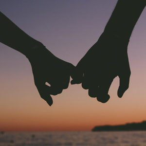 two people holding hands at sunset because they're trying casual dating