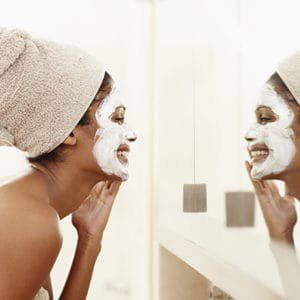 a woman with hyperpigmentation putting on a face mask in the mirror