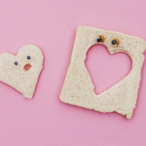 two slices of cut out bread with eyes to represent love at first sight