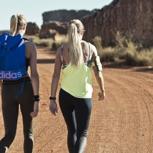 two women walking on a dirt path