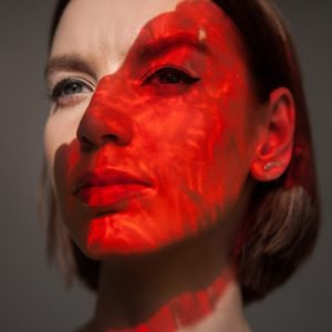 Red light on face of young model to represent a story about how to manage rosacea