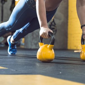 close-up of a personal trainer on kettlebells doing a full-body workout