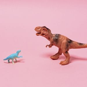 one-sided relationship — Big and Small Toy Dinosaurs on Pink Background.